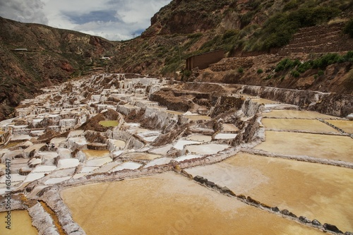 Salt ponds, Maras. Peru, South America and cloudy blue sky