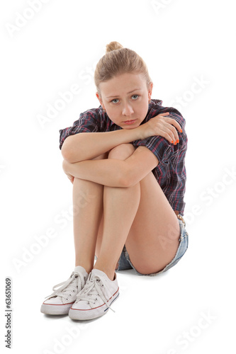 Sad girl sitting on a white background