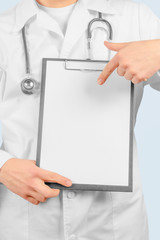 Physician is pointing on clipboard, copyspace