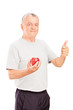 Mature man holding an apple and giving thumb up