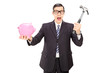 Scared businessman holding hammer and a piggybank