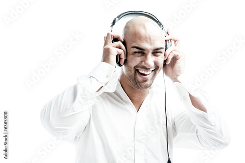 white dressed man smiling while holding his headphones