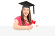 Smiling girl with diploma posing behind blank panel