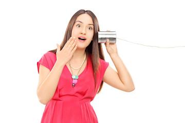 Woman hearing something through a tin can phone
