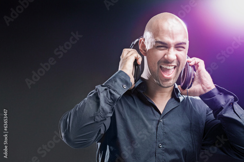 Dj having fun and holding his headphones