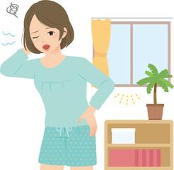 朝の室内で眠そうにあくびする若い女性