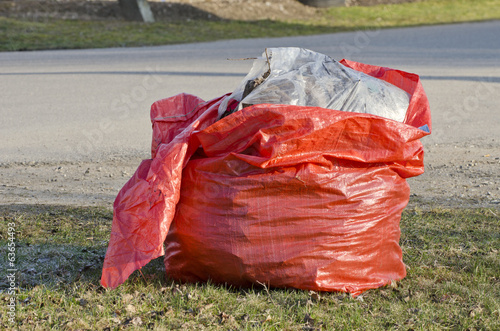 open red plastic rubbish bag sack in park