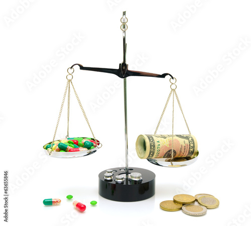 medical drugs and money on scales on white background