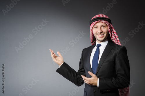 Arab businessman pointing to something or somebody against grey