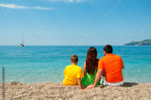 Happy family: Mom, Dad and son sitting on the beach