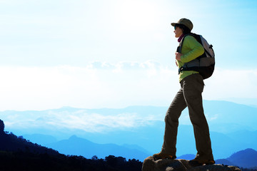 Female hiker against blue mountain background.