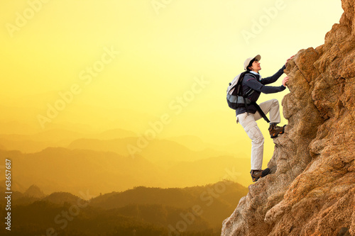 Female hiker climbing rocks.