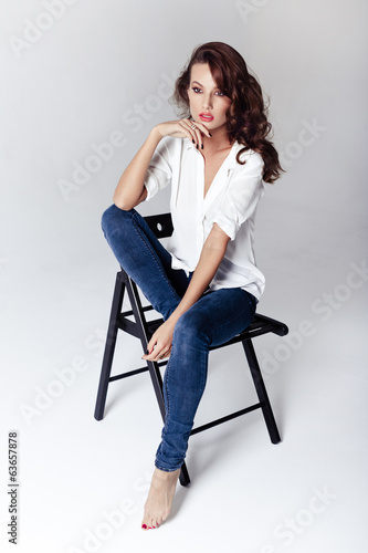 Fashion model sitting on a chair in a blouse and jeans barefoot