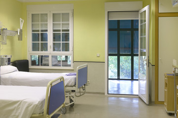Hospital room with beds and furniture.