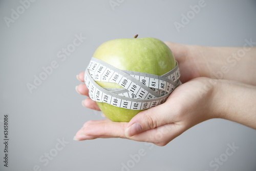 Green apple in female hands