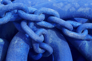 Iceland. Rusted metallic chain in blue tone close up.