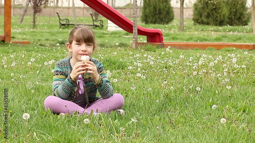 little girl sitting on grass and eat ice cream