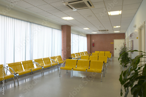 Hospital waiting area with yellow metallic chairs.