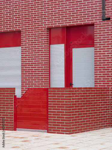 Red building facade with patio.