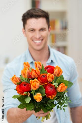 canvas print picture lächelnder mann überreicht blumen