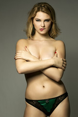 glamour portrait of a pretty blonde girl covering her nude body