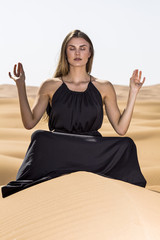 Yoga position in the desert on the sand