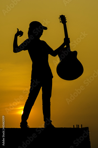 Young girl with guitar,silhouette