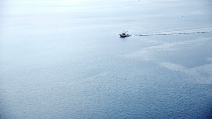Fishing boat at blue calm sea aerial view