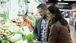 Couple shopping, looking at vegetables in vegetable market