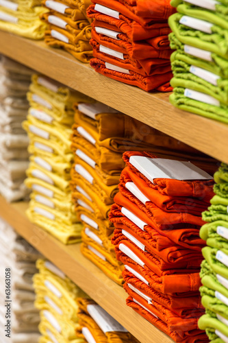 Neat stacks of folded clothing on the shop shelves