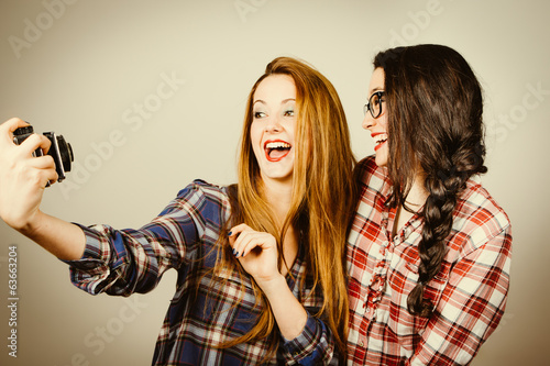 Hipster girls making a selfie with an old camera