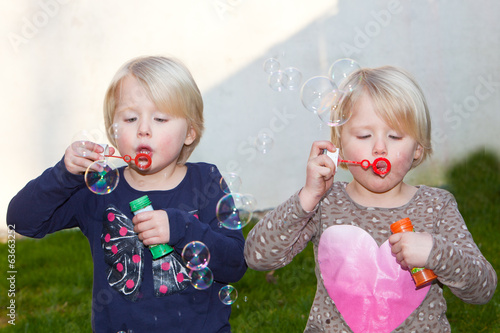 canvas print picture Two beautiful blond twins blowing bubbles