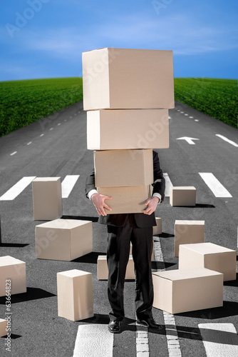 Business man holding carton boxes on the road with a lot of boxe