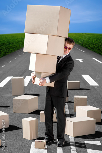 Business man holding carton boxes on the road