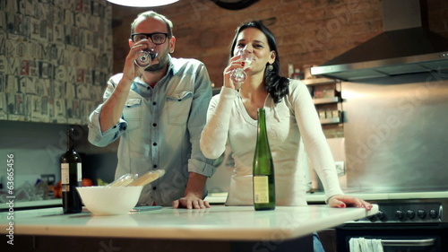Young couple raising toast with wine, celebrating in kitchen