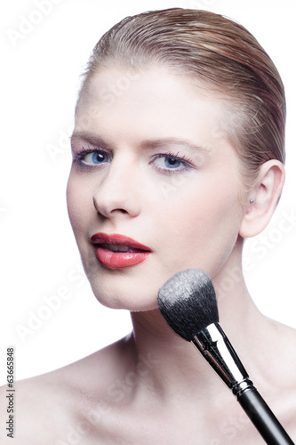 Blonde beauty with cosmetic brush isolated on white