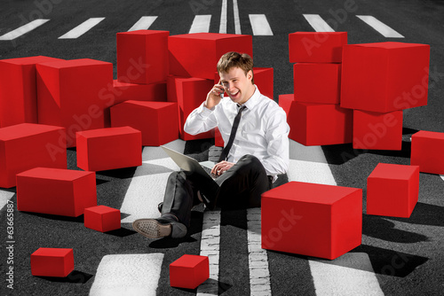 Confident and successful businessman sitting on the road and spe