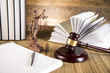 Leinwanddruck Bild - Lady of justice, wooden & gold gavel and books on wooden table