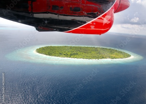 tropical island under a plane wing