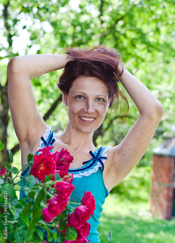 woman of middle age near to a bush of roses