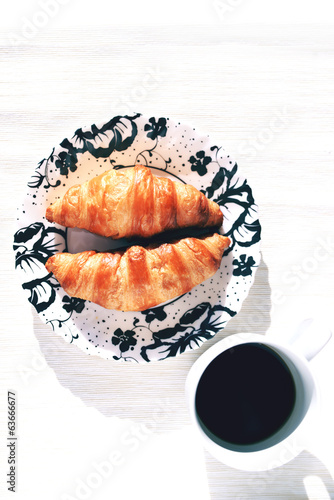 French croissants on a plate and black coffee cup