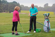 Lady golfer being taught by a golf pro.