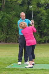 Golf pro correcting a lady golfers grip