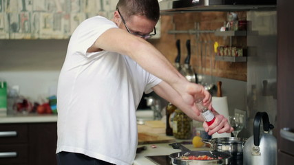 Young man cooking, adding spices to frying meal in kitchen