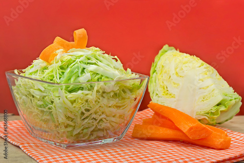 Bowl of green cabbage salad decorated with carrot.