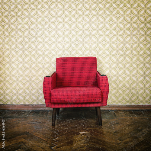 Vintage room with old fashioned red armchair, wallpaper and weat