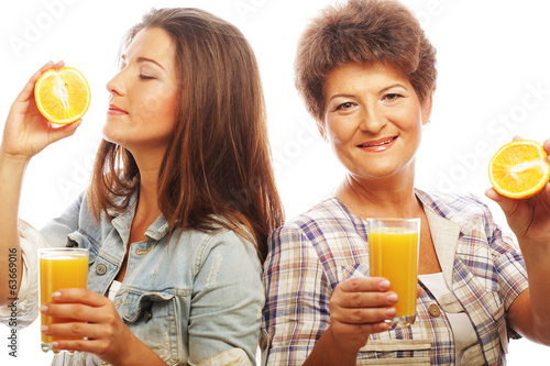 mother and daughter drinking orange juice