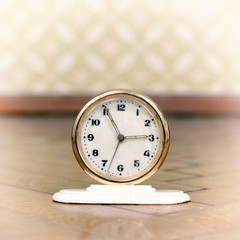 Retro clock on the weathered wooden parquet floor in vintage roo