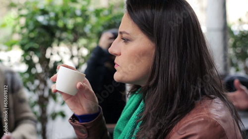 Pensive woman drinking coffee in outdoor cafe