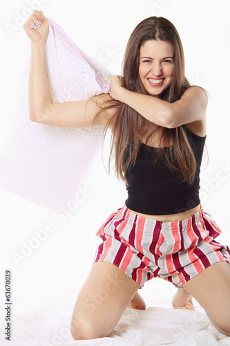 Beautiful girl playing and joking with a pillow